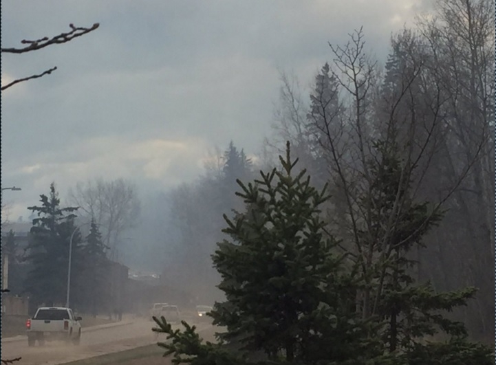Smoke billows on to a roadway in Abasand Heights from a wildfire on April 30, 2016 // Lauren O'Hare - Harvard Broadcasting